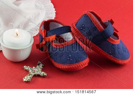 Christening background with navy and red booties candle and Christian cross pendant