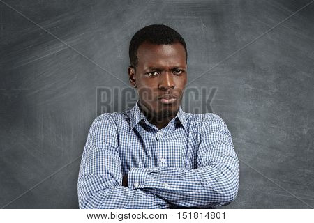 Headshot Of Angry Serious African Teacher With Arms Folded, Dissatisfied With His Misbehaving Studen