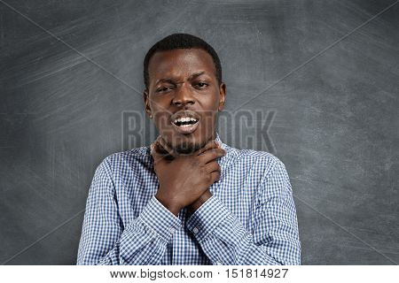 Annoyed Grumpy Young African Teacher Or Student In Casual Shirt Holding Himself For Neck, Making Sui