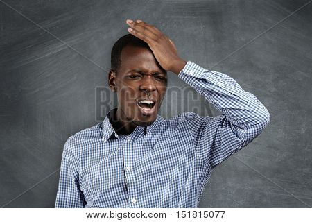Human Face Expressions And Emotions. Forgetful Dark-skinned Man Holding His Hand On His Head With A