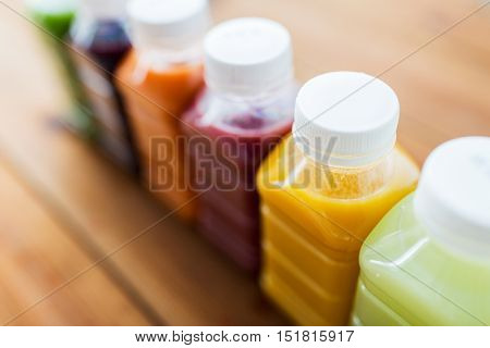 healthy eating, drinks, dieting and packaging concept - close up of plastic bottles with different fruit or vegetable juices on wooden table