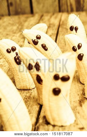 Funny halloween fruit photo on banana ghosts on party decoration table. Creepy event food