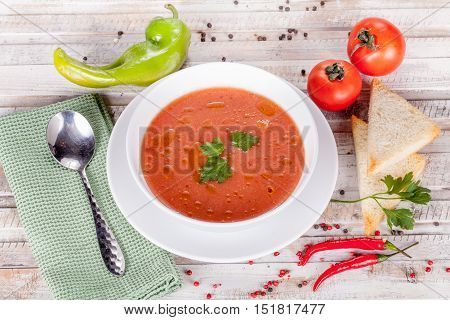 Tomato soup on white table with ingridients