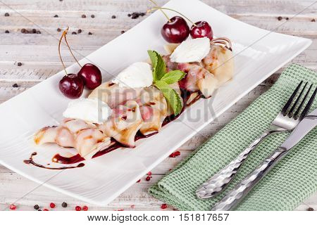 Russian dumplings with cherries on white table