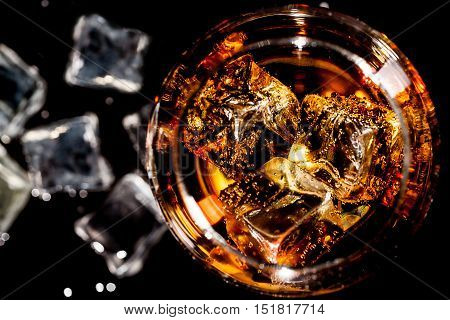 glass of whiskey with ice top view