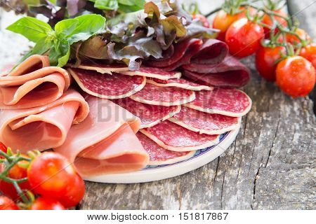 Antipasto with ham salami and bresaola. tomato and basil. selective focus. poster