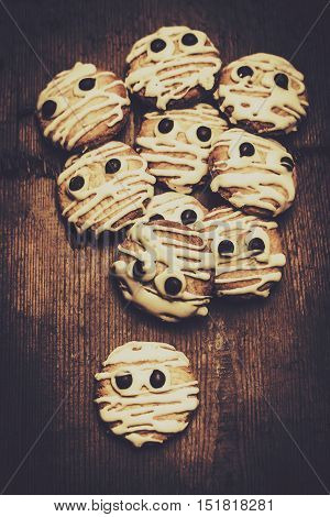 Halloween cooking conceptual of frightening monster cookies wrapped in bandages of melted white chocolate. Fright night party baking