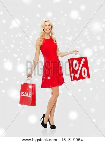 people, sale, christmas, winter and holidays concept - happy young woman in red dress with shopping bags over snow background