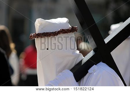 Hooded man does penance with the cross on his shoulders