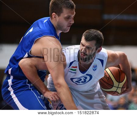 KAPOSVAR, HUNGARY - OCTOBER 6: Peter Grebenar (in white) in action at Hungarian Championship basketball game with Kaposvar (white) vs. Sopron (blue) on October 6, 2016 in Kaposvar, Hungary.