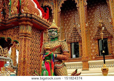 Nakhon Pathom Thailand - December 27 2005: Giant Yak guardian demon stands in front of the intricately carved designs of the Ubosot at Wat Dai Lom