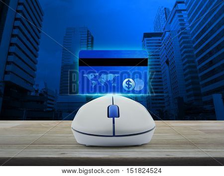 Wireless computer mouse with blue credit card on wooden table over city tower background Online e-payment concept