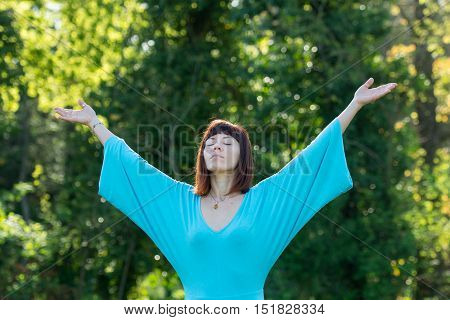 Woman doing yoga exercise, tree in background