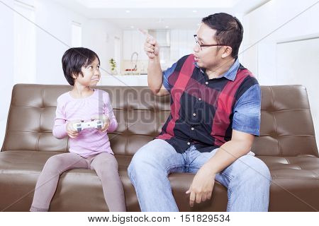 Portrait of a young father scolding his daughter to stop playing video game at home