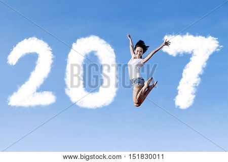 Concept of New Year 2017. Picture of a joyful woman jumping on the blue sky with number 2017