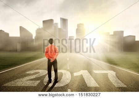 Male entrepreneur standing on the street while looking at a town with number 2017