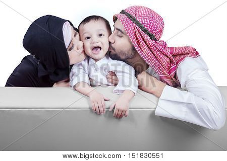 Portrait of two middle eastern parents sitting on the sofa while kissing their son cheek isolated on white background