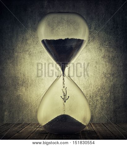 Young man falling inside a hourglass with black sand. Time management productivity concept. Human aging process and age related illness.