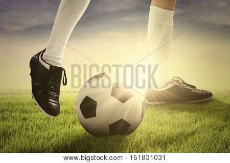 Foot of soccer player playing a ball on the green field at sunrise time in the morning