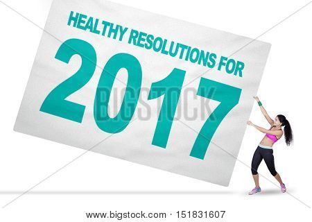 Healthy Indian woman pulling a big banner with text of healthy resolution for 2017 isolated on white background