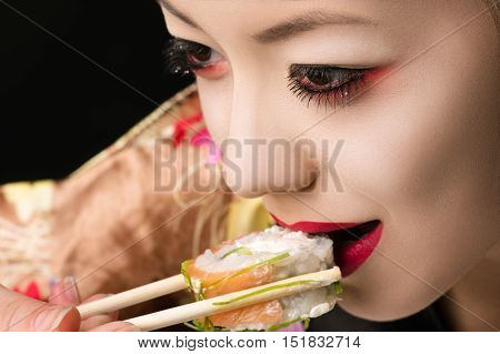 korean teenager girl with bright makeup eating sushi closeup