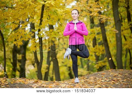 Sporty beautiful happy young woman practicing yoga, standing in Tree posture, Vrikshasana, working out outdoor on autumn day wearing sportswear sweatshirt. Full length portrait