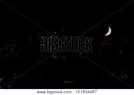 A gibbous moon close to set down over a urbanized hill