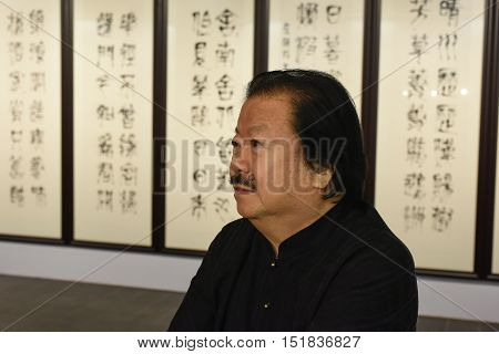 Saint-Petersburg Russia - September 12 2016: The richest Chinese artist Cui Ruzhuo to the opening of his exhibition in the Central Exhibition Hall on the background of his paintings.