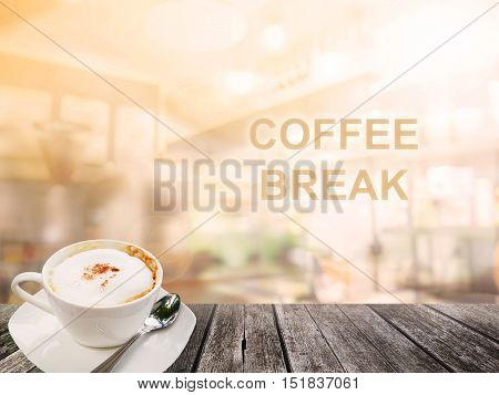 A cup of hot coffee on wood surface with abstract blur coffee shop background