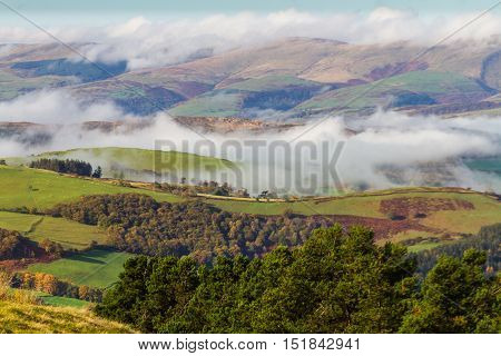 Welsh countryside with cloud clinging to hills in temperature inversion. Powys Wales United Kingdom.