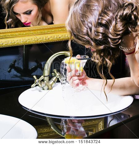 Pretty young sexy woman or girl with blond curly hair and fashion makeup gaining water and drinks it from glass with lemon indoor
