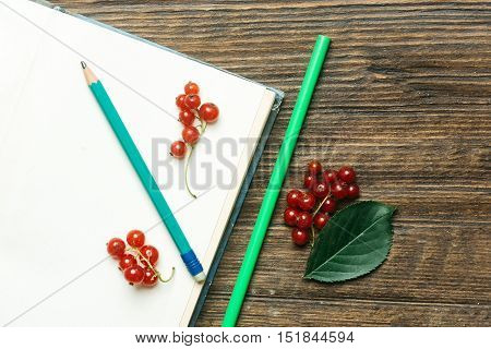 Green graphite pencil on white page of open diary fresh red currant leaf and straw on wooden background