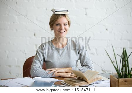 Portrait of a young smiling woman at the desk with books on her head, sitting straight, looking at the camera. Education concept photo
