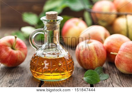 apple cider vinegar in a bottle nad fresh fruits with leaves
