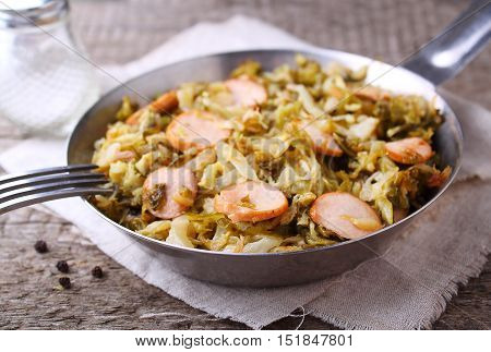 Cabbage stew with sausages in a frying pan on a wooden background