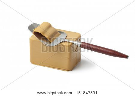 Piece of norwegian flotemysost cheese and slicer on white background