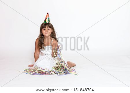 Cute smiling tanned little girl in white dress with paper hat on her head is sitting on the white background looking at the camera. Free place for yout text is in the right side of the photo.