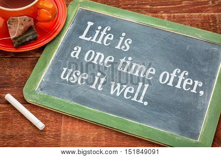 Life is one time offer, use it well  - motivational text on a slate blackboard with chalk and cup of tea