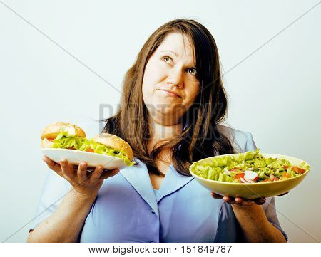 fat white woman having choice between hamburger and salad close up, unhealthy food concept