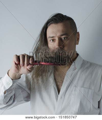 a man looking at a hairbrush with a loosing hair