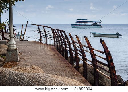 A broken and rusty railing along a seawall with some boats in the back ground