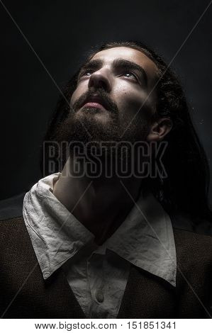 low key portrait of bearded medieval peasant looking at the top to the light