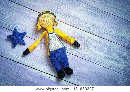 Handsome Boy Doll On Blue Wooden Boards. Handmade Crochet Soft Doll Toy.