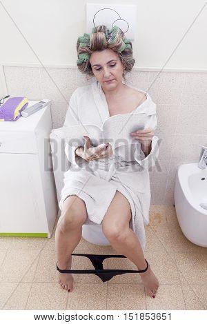 Beautiful Lady Sitting On The Toilet Reading A Magazine