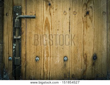 Wooden trap door with iron latch - Latch and wooden planks part of an aged door from a german warehouse with copy space on the right side for your text.