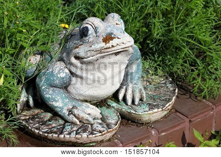 Shabby old frog statue in a garden.