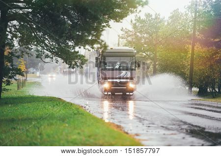 Lorry on wet road was in a deep puddle and created a large flow of water that has become an obstacle to the flow of oncoming cars.