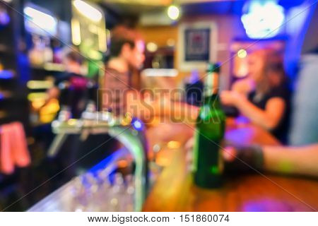 Blurred defocused side view of people drinking beer and having fun at cocktail bar restaurant - Social gathering concept with people enjoying time together - Vivid filter with blurry bokeh composition