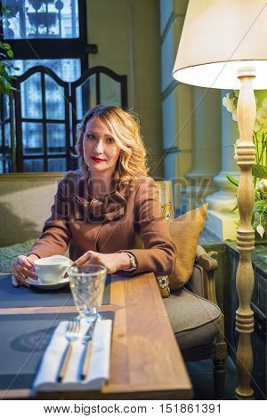 Middleaged blonde woman sits with tea and looks at camera in cozy restaurant