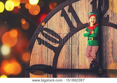 Christmas concept. Little Elf child on clockwise